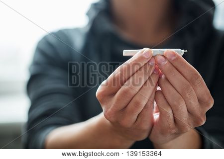 drug use, substance abuse, addiction and people concept - close up of addict hands with marijuana joint