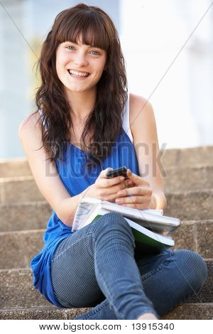 Teenage Student Sitting Outside On College Steps Using Mobile Phone