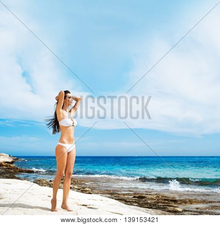 Young, beautiful, sporty and sexy woman in swimsuit. Girl posing on a beach at summer. Sea and sky background.