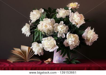 Still life with a bouquet of peonies open book and seashells on the table with a red tablecloth.