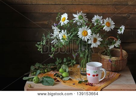 Summer still life with a bouquet of daisies gooseberries and apples in a rustic style.