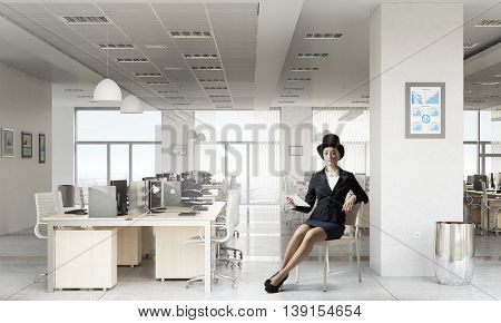 Businesswoman on chair in office . Mixed media