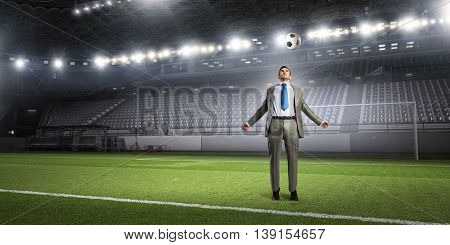 Businessman kicking ball . Mixed media