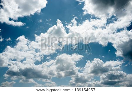 Blue summer sky with curvy clouds, void. Great bright background for life-loving advertisement