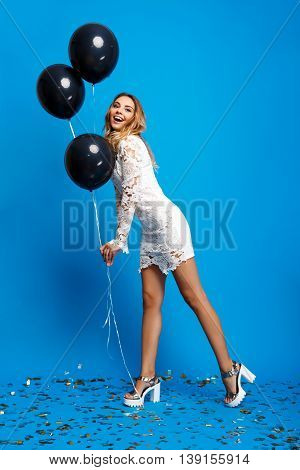 Portrait of young beautiful blonde girl in dress looking at camera, holding baloons, smiling, resting at party over blue background.