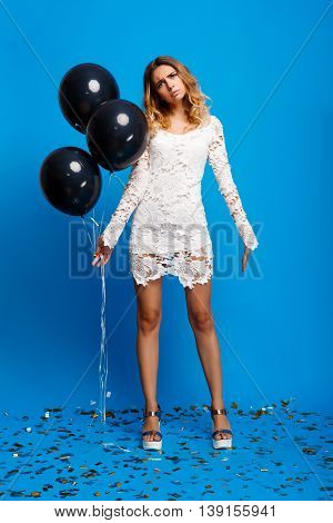 Portrait of young beautiful blonde girl in dress looking at camera, holding baloons, resting at party over blue background.