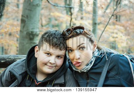 Crazy woman with son posing in the autumn deciduous forest. Hiking theme. Seasonal natural scene. Portrait of travellers.