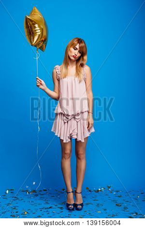 Portrait of young beautiful girl in dress holding baloon,  resting at party over blue background.