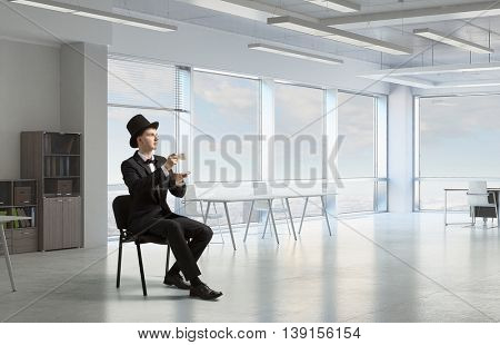 Businessman in cylinder drinking coffee . Mixed media