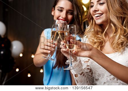Three young beautiful girls in dresses clinking glasses with champagne, speaking, smiling, laughing, resting at party.