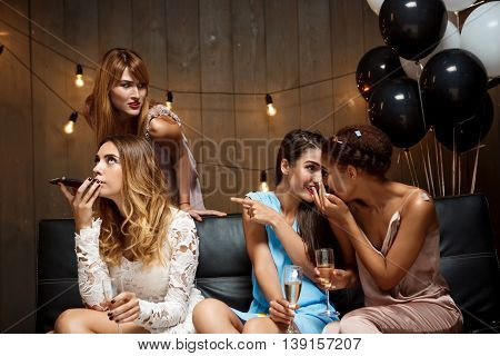 Four young beautiful girls in dresses speaking, gossiping, drinking champagne, resting at party.
