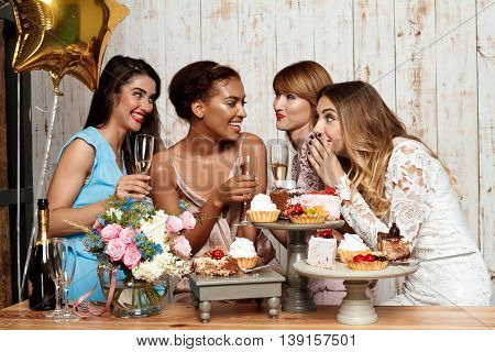 Four young beautiful girls in dresses smiling, laughing, speaking, gossiping, drinking champagne, resting at party over blue background.