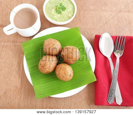 Indian snack, Mangalore bajji, made from deep-frying batter of refined wheat flour and yogurt, native to Mangalore city, Karnataka state, India, with tea and chutney.