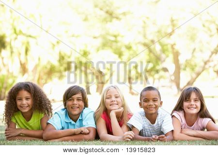 Group Of Children Lying On Stomachs In Park