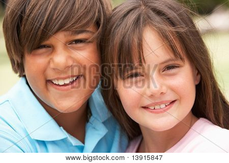 Two Children In Park Giving Each Other Hug