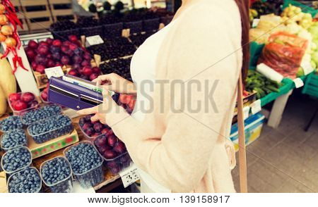sale, shopping, pregnancy and people concept - close up of pregnant woman with wallet and and money buying food at street market