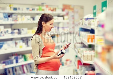 pregnancy, medicine, pharmaceutics, health care and people concept - happy pregnant woman with smartphone choosing medication at pharmacy