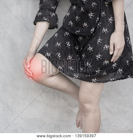 Female holding hand on spot knee pain.