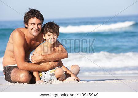 Father And Son Wearing Swimwear Sitting On Sandy Beach