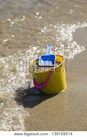 Toy Spade and Bucket on a Beach Shore.