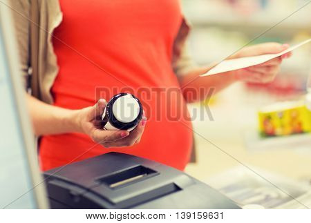pregnancy, medicine, pharmaceutics, health care and people concept - close up of pregnant woman with prescription buying medication at pharmacy cash register