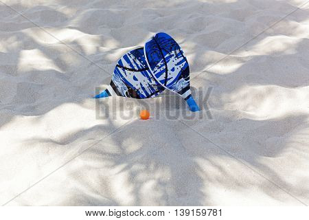 beach tennisIn palms shadow there are rackets and a ball on the sandSet for ping pong