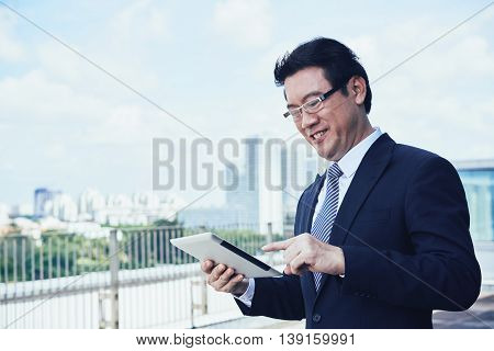 Smiling Vietnamese businessman standing outdoors and using digital tablet