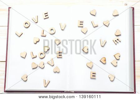 The Word Love A Lot Of Hearts On A Background Of Book On A Wooden Table