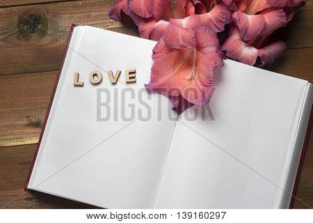 Open Book On Light Table. The Word Love And Flower On A Background Of Book. Back To School. Copy Spa