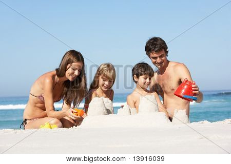 Family Building Sandcastles On Beach Holiday