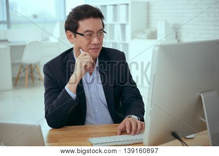 Mature Asian businessman working on computer in office