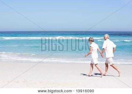 Casal sênior de férias ao longo da praia