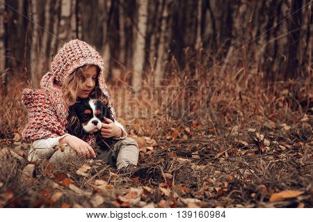 child girl relaxing with her cavalier king charles spaniel dog in autumn forest wrapped in cozy scarf