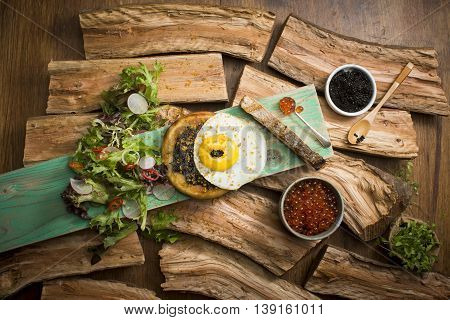 Caviar with omelette egg and salad on wood background