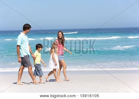 Family Walking Along Sandy Beach
