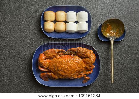 Fried crab on blue plate with chinese dumplings on grey background