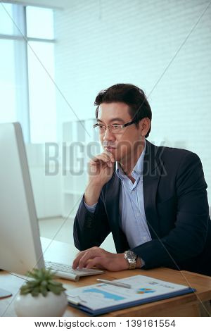 Pensive financial manager reading information on computer screen