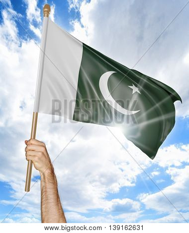 Person's hand holding the Pakistani national flag and waving it in the sky, 3D rendering
