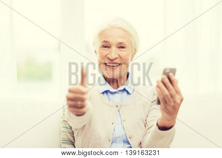 technology, communication, gesture age and people concept - happy senior woman with smartphone and showing thumbs up at home