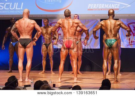 MAASTRICHT THE NETHERLANDS - OCTOBER 25 2015: Male bodybuilders flex their muscles and show their best physique in a back pose on stage at the World Grandprix Bodybuilding and Fitness of the WBBF-WFF