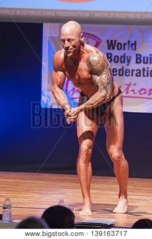MAASTRICHT THE NETHERLANDS - OCTOBER 25 2015: Male bodybuilder Erik Stobbe flexes his muscles and shows his best physique in a most muscular pose on stage at the World Grandprix Bodybuilding and Fitness of the WBBF-WFF
