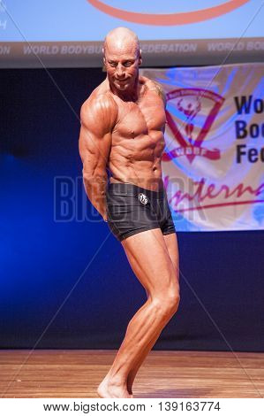 MAASTRICHT THE NETHERLANDS - OCTOBER 25 2015: Male bodybuilder Erik Stobbe shows his best triceps pose at the World Grandprix Bodybuilding and Fitness of the WBBF-WFF on October 25 2015 at the MECC Theatre in Maastricht the Netherlands.