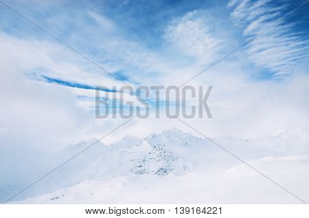 Snow-covered Mountains And Blue Sky With White Clouds.