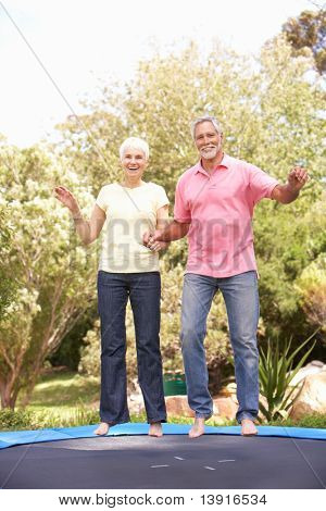 Senior Couple Jumping On Trampoline In Garden