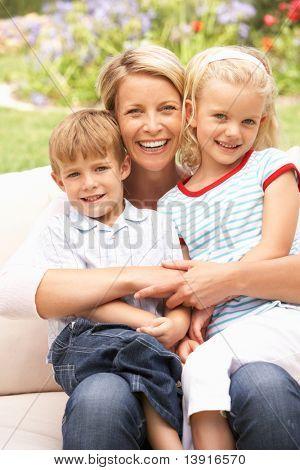 Mother And Children Relaxing In Garden