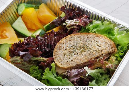 Healthy food delivery and diet concept. Take away of fitness meal. Weight loss lunch in foil boxes. Whole-grain sandwich with boiled beef and fresh vegetables closeup at white wood