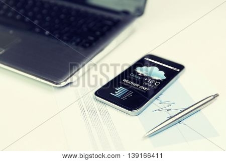 business, technology forecast and meteo concept - close up of smartphone with weather cast on screen, laptop computer and pen on office table