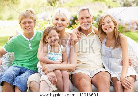 Grandparents And Grandchildren Relaxing In Garden