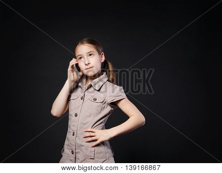 Portrait of serious girl speak on mobile phone at black background. Female child talking to somebody, calling with cell phone. New generation devices, communication