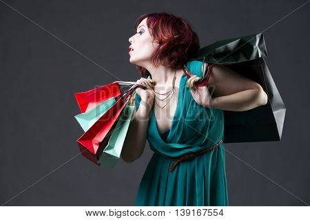 Shopaholic concept young beautiful red-haired caucasian woman in aquamarine dress posing in studio on gray background professional makeup and hairstyle expressive portrait